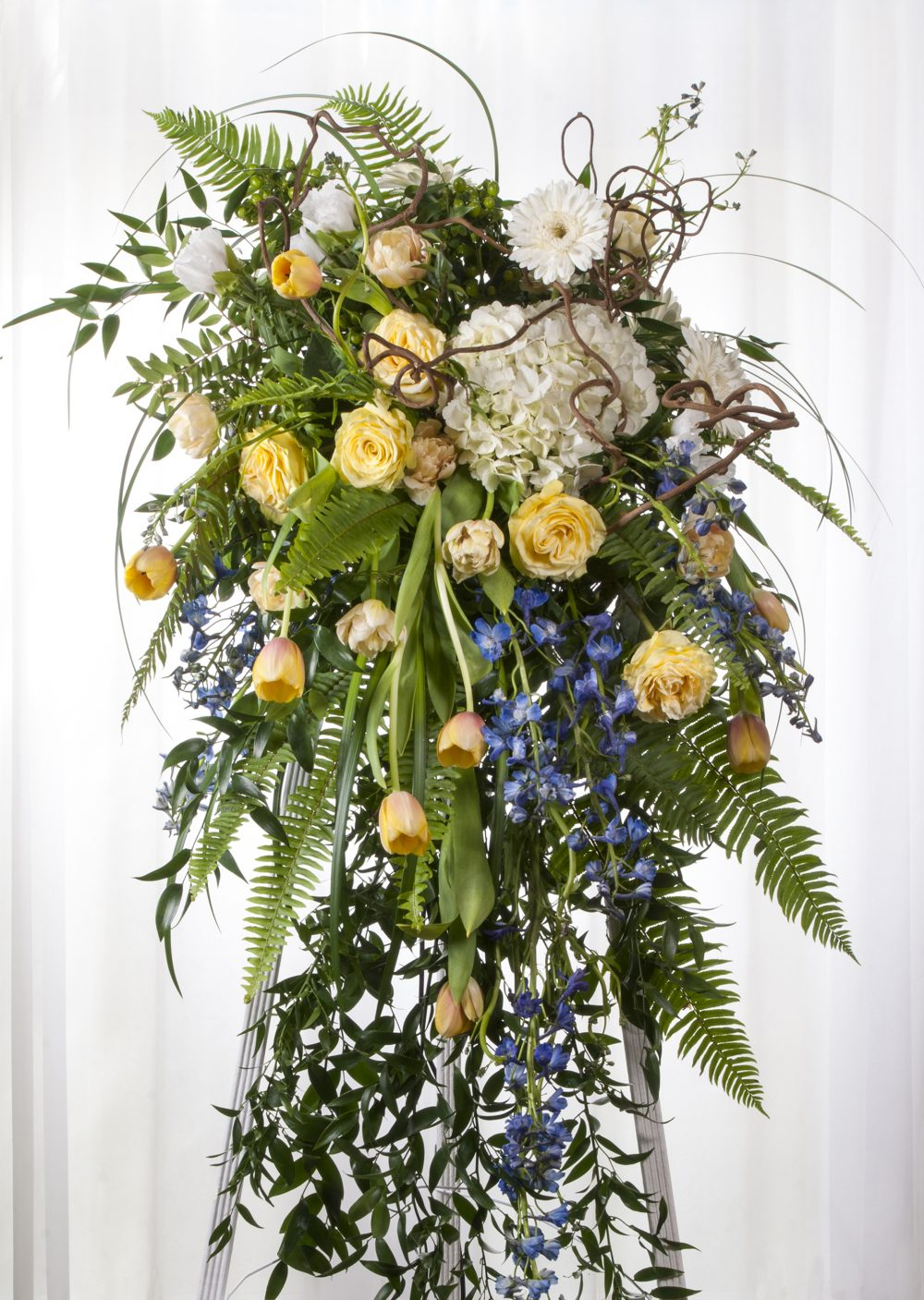Unique beautiful funeral flower arrangement in an elegant standing spray, mounted on an easel.