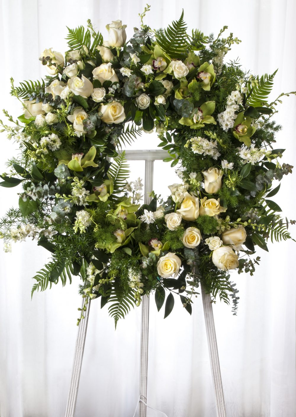 Unique beautiful funeral flower arranged in a lovely cut flower wreath, mounted on a wooden easel.