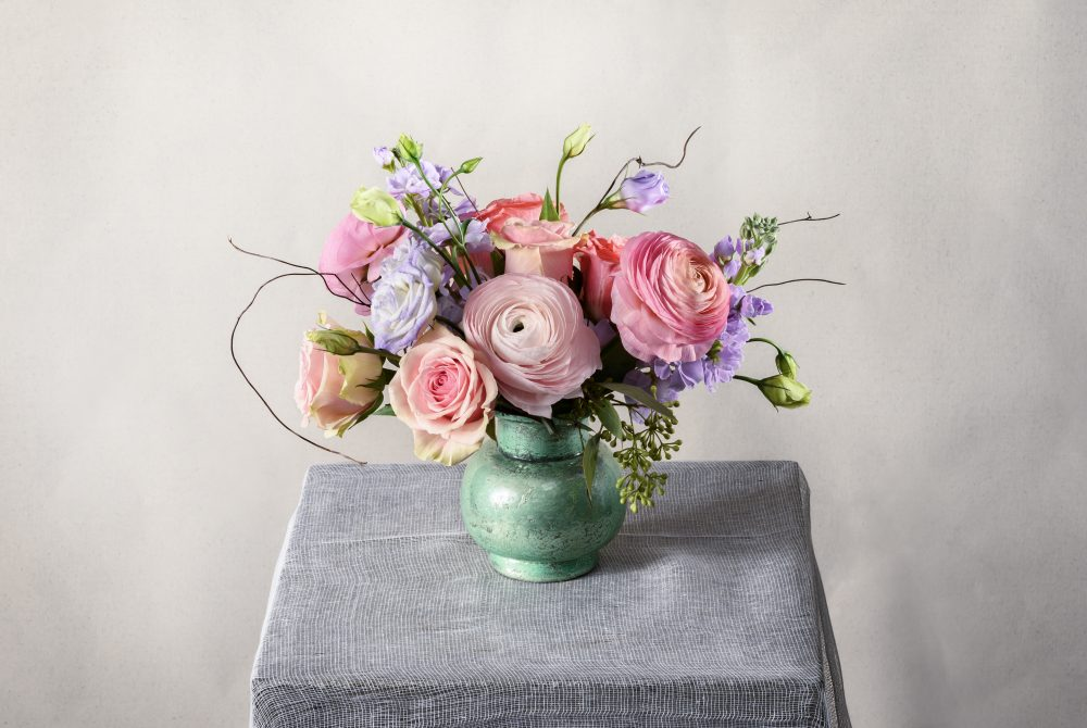 Pretty pastel spring flowers arranged in a charming aqua pot.