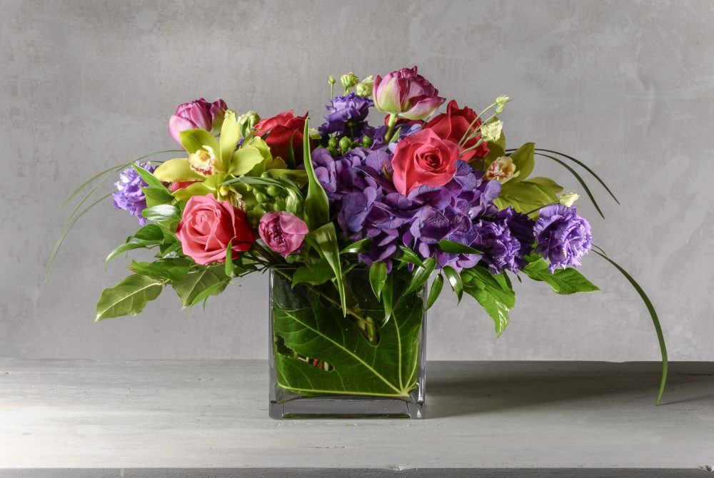 Mother's Day arrangement of fresh flowers in vibrant purple, green, and bold pink colors.
