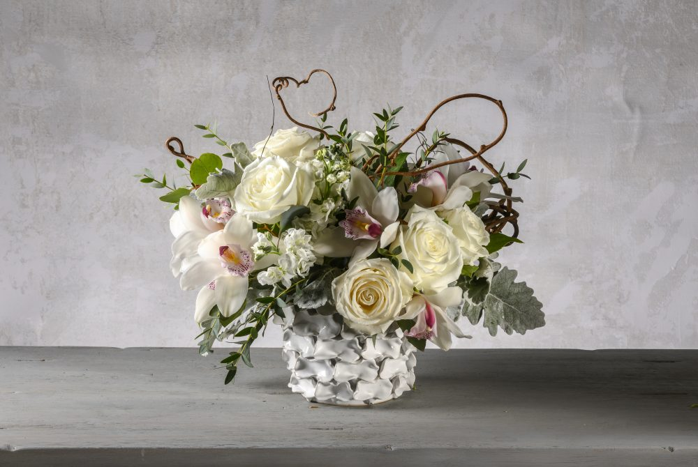 Fresh flower arrangement of white blossoms in a white ceramic cachepot.