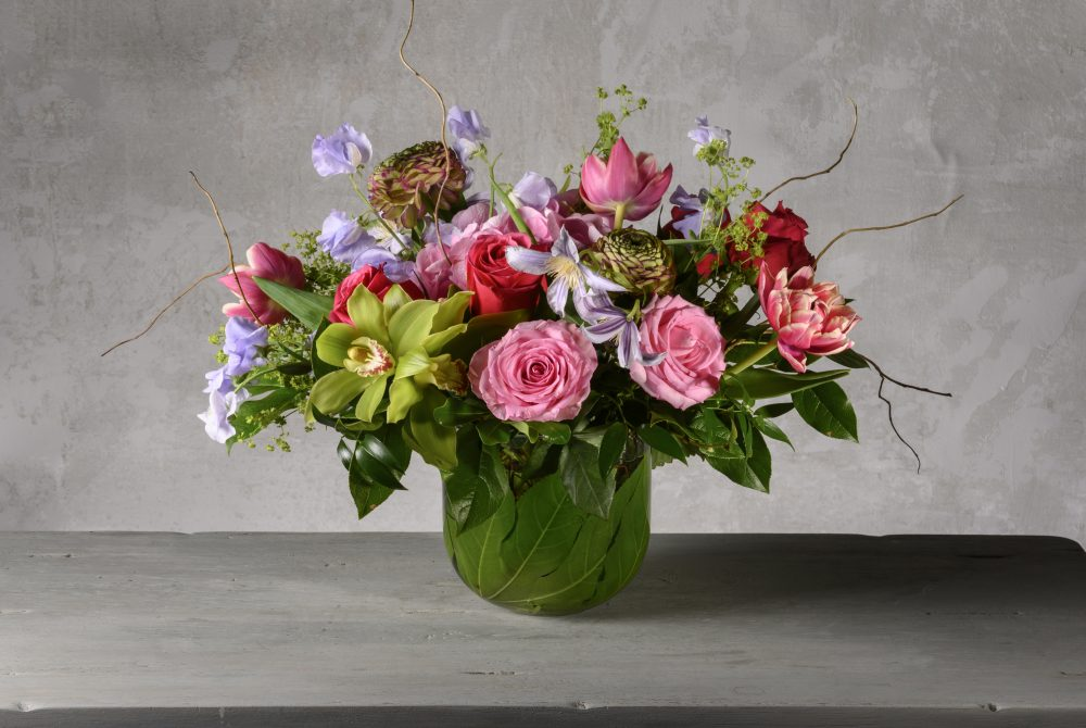 Bright spring flowers arranged with pink, green, and lavender blossoms.