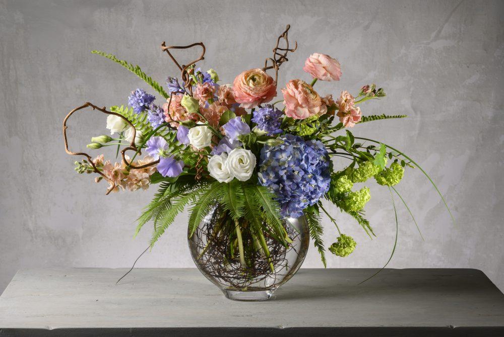 Bright pastel spring blossoms in a lush fresh flower arrangement.