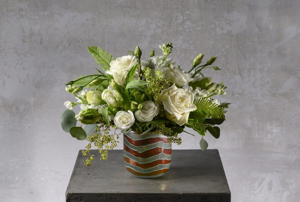 White spring flowers arranged in an artful sanded glass votive.