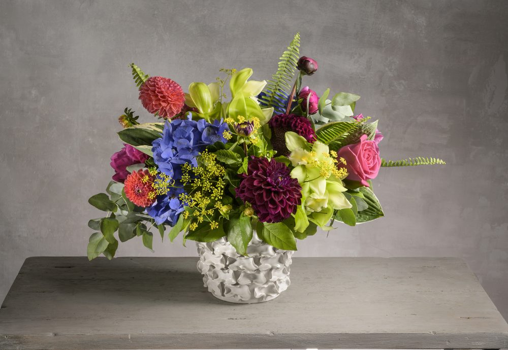 Bright summer flowers arranged with coral, green, purple and magenta blossoms.
