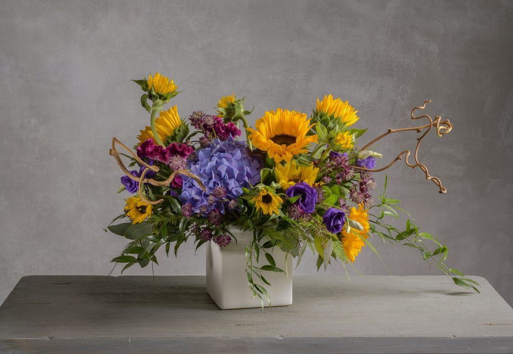 A fresh flower arrangement with bold yellows and purples.