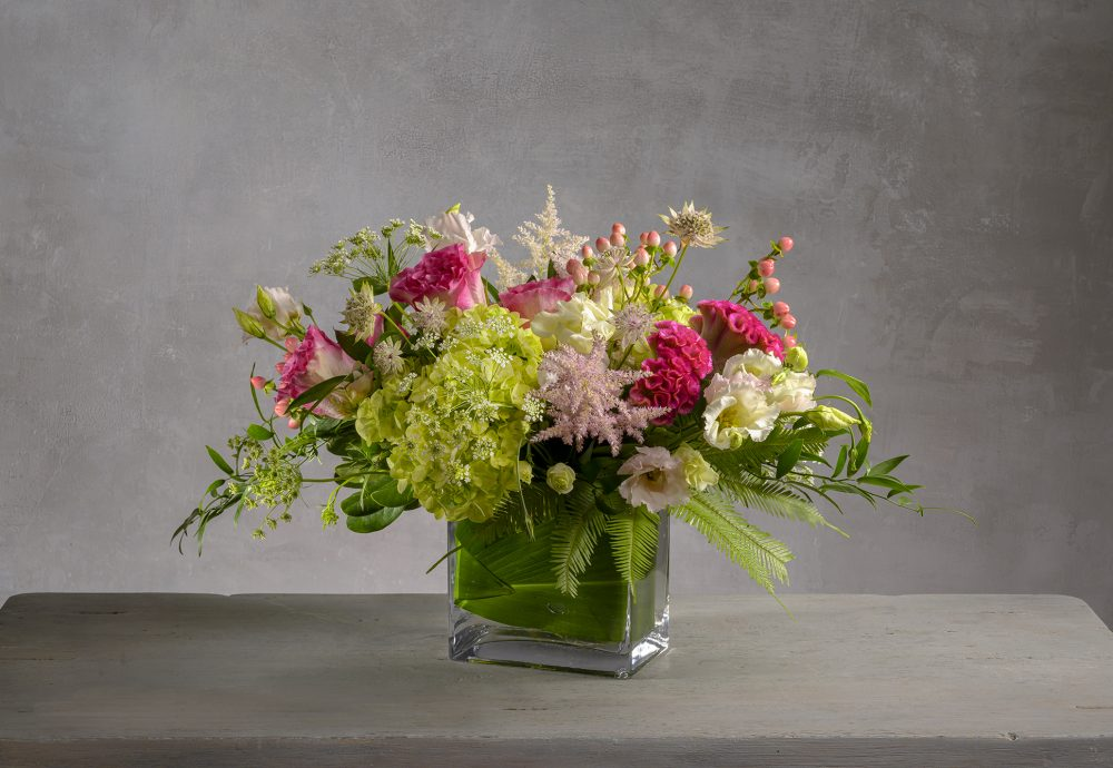 Fresh flower arrangement of pink, green and white blossoms in a glass rectangle.