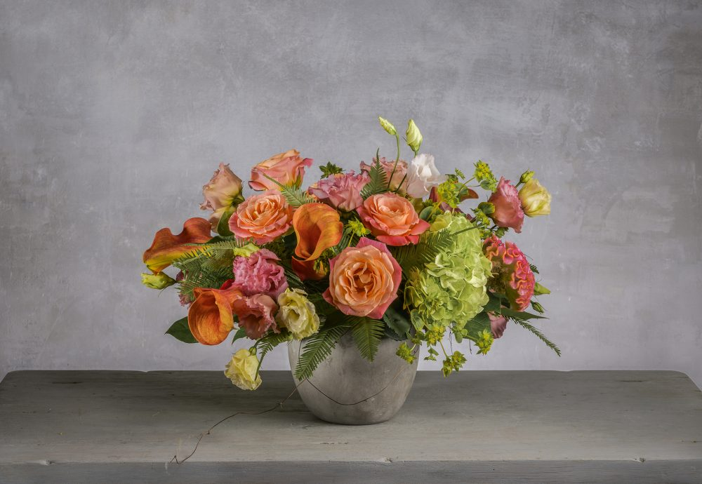 Summer arrangement of fresh flowers in vibrant coral, orange, and pink colors.