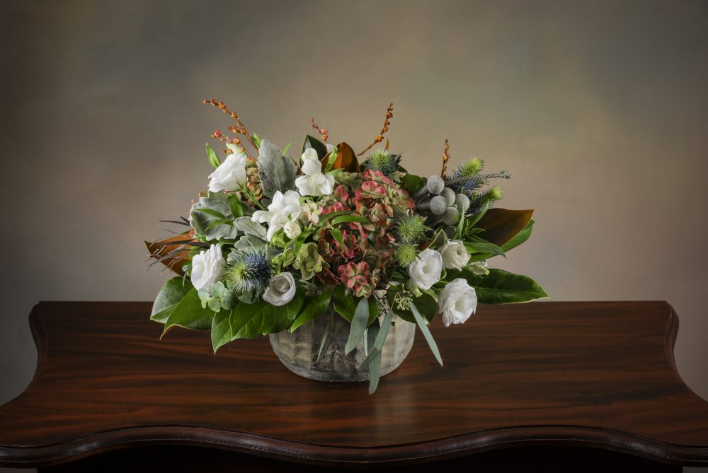 Rich autumn foliage, magnolia and flowers in a matte metallic pot