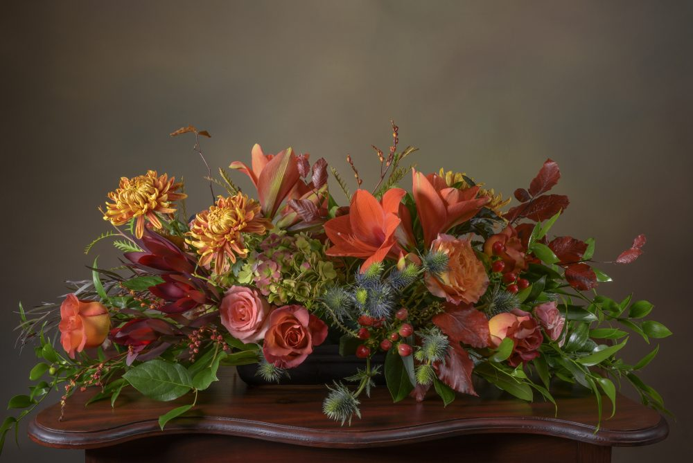 Rich autumn blossoms, berries, pods and foliage in a long and low fresh flower arrangement