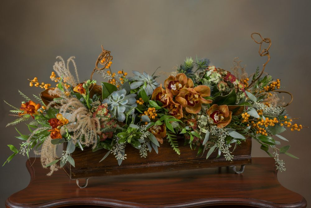 Soft autumn blooms, berries, and grasses in a long and low fresh flower arrangement