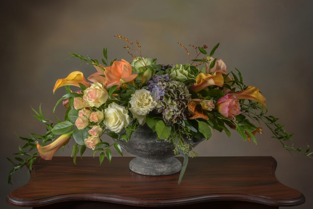 Bright and pastel autumn blossoms, pods and foliage in an aged pedestal fresh flower arrangement