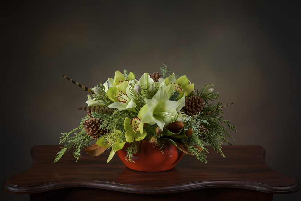 Bright green flower arrangement with evergreens and magnolia in a red glazed bowl