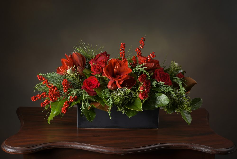 Bold red blossoms, berries, and evergreens in a long and low fresh flower arrangement