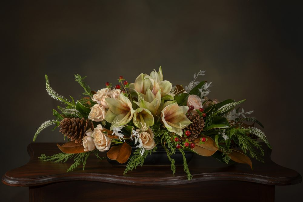 Pastel winter flowers and foliage in a low holiday centerpiece