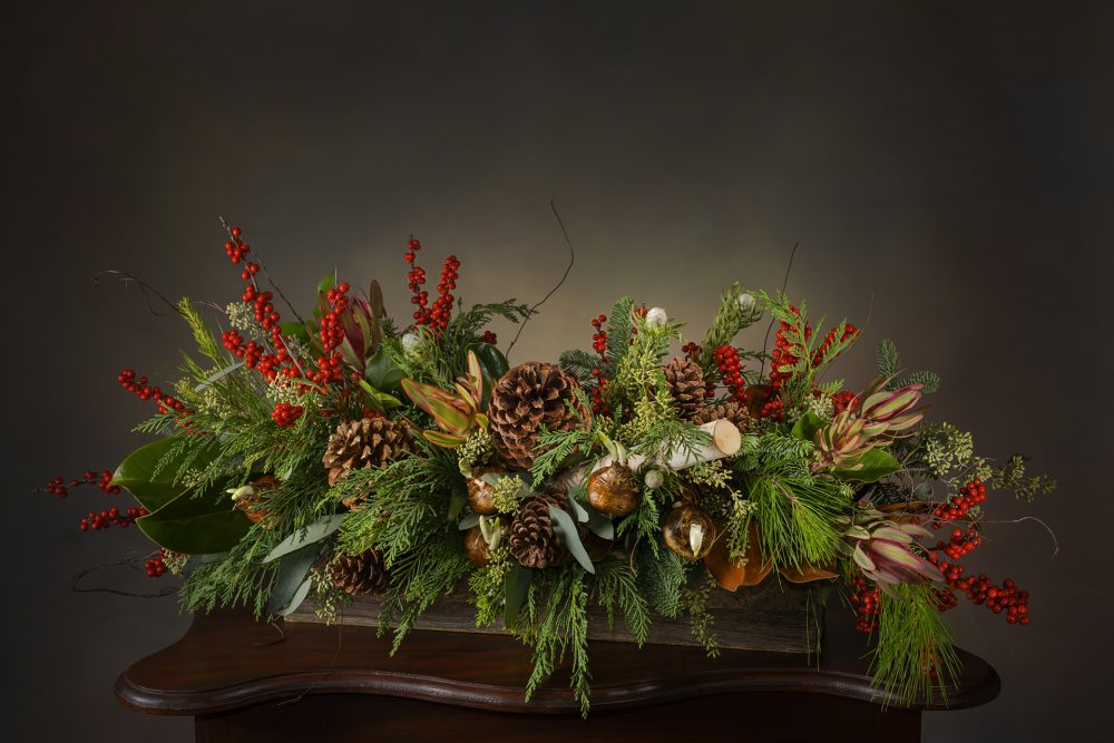 Fresh woodland evergreens, berries, pods and birch in a low centerpiece