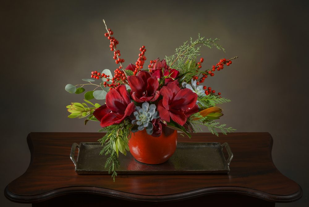 Fresh holiday flower arrangement in red glazed pot.