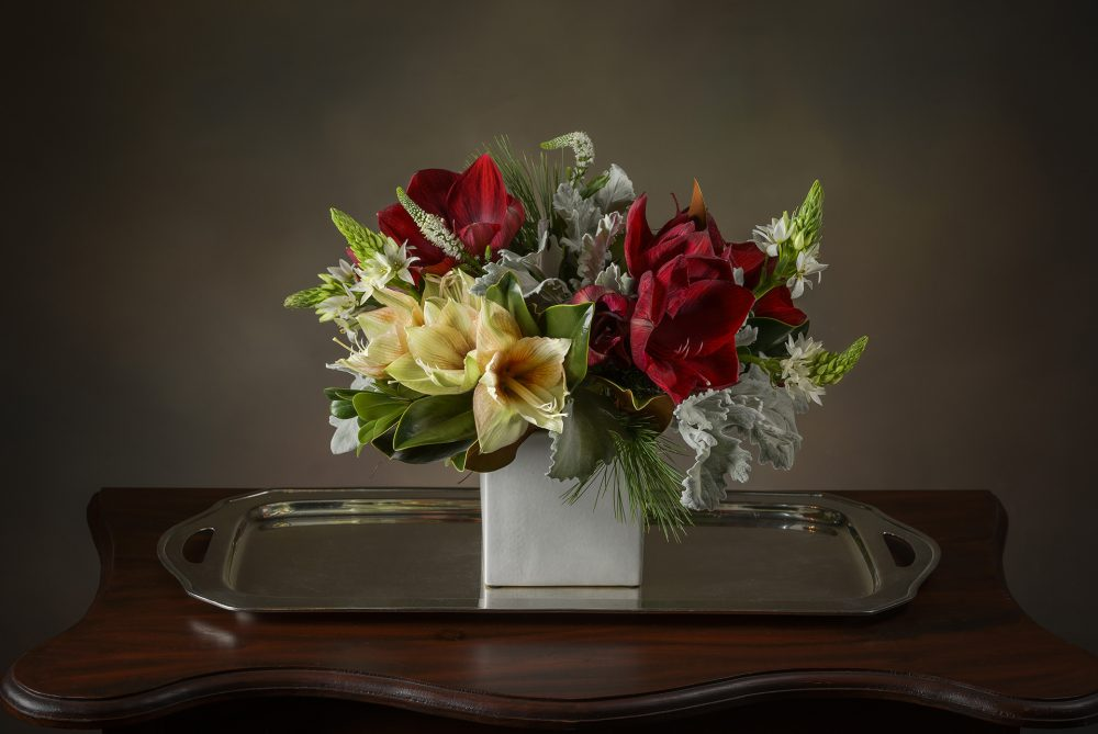 Deep red and white arrangement of fresh flowers with evergreens