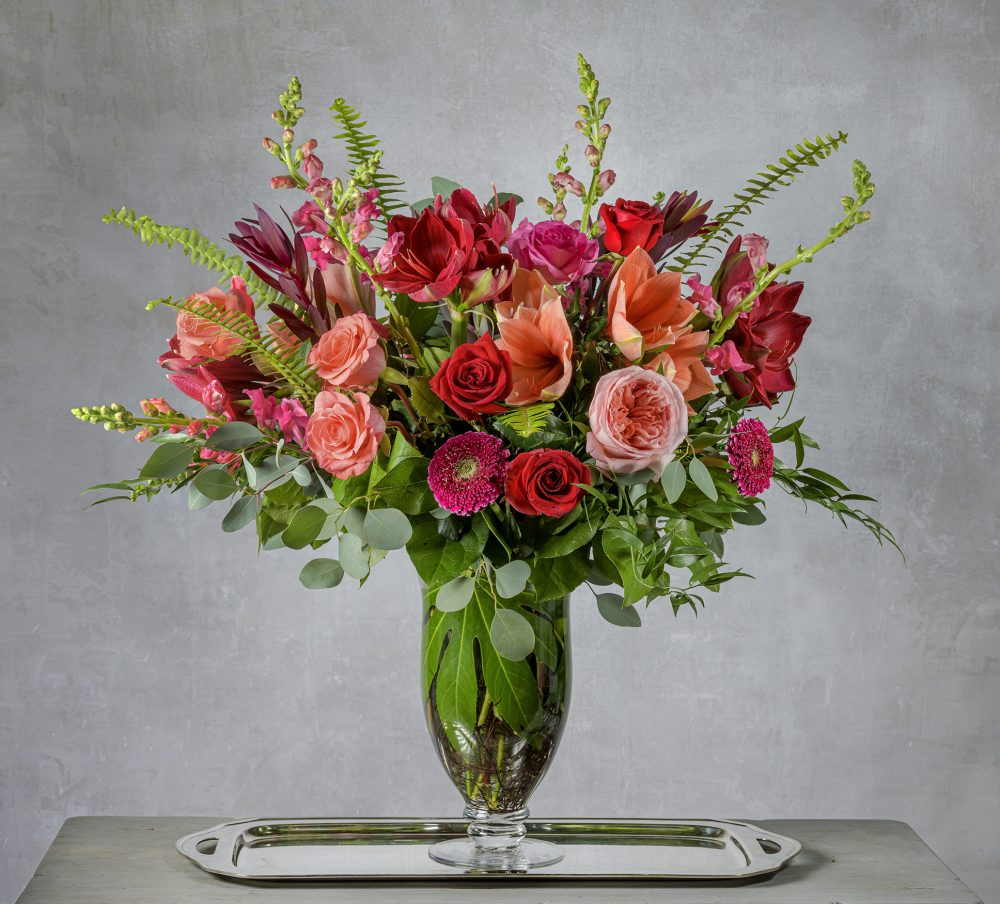 Fresh Valentine flowers in a vibrant pink, coral, and red tall flower arrangement.