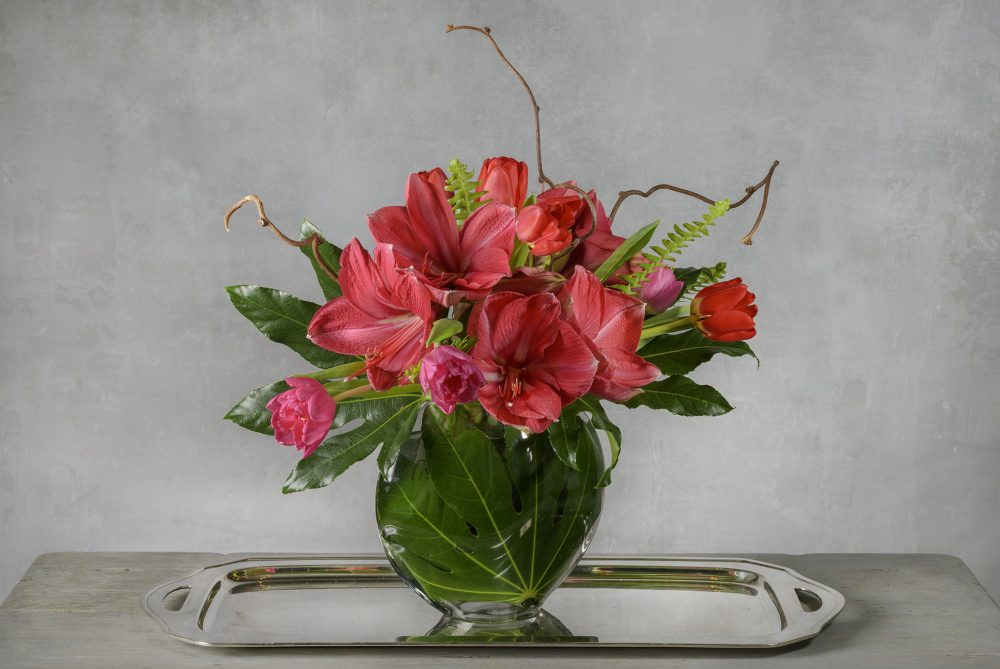 Vibrant magenta pink with red blossoms in a fresh flower arrangement.