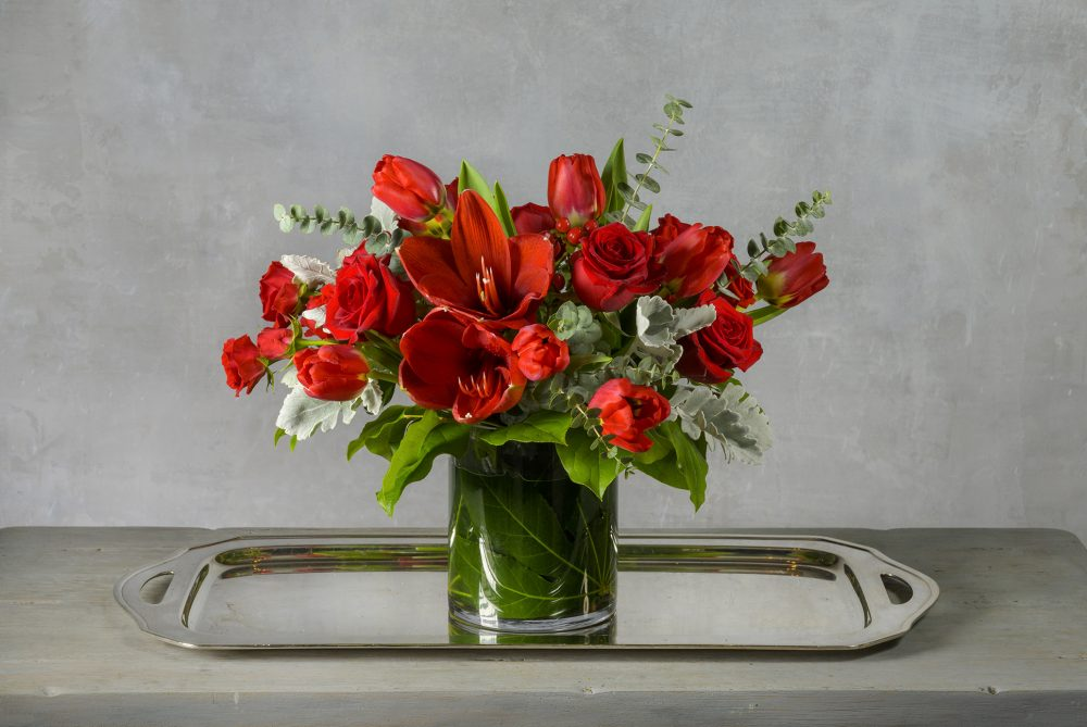 Passion red Valentine fresh flower arrangement with red roses, tulips, and amaryllis in an emerald leaf-lined cylinder.