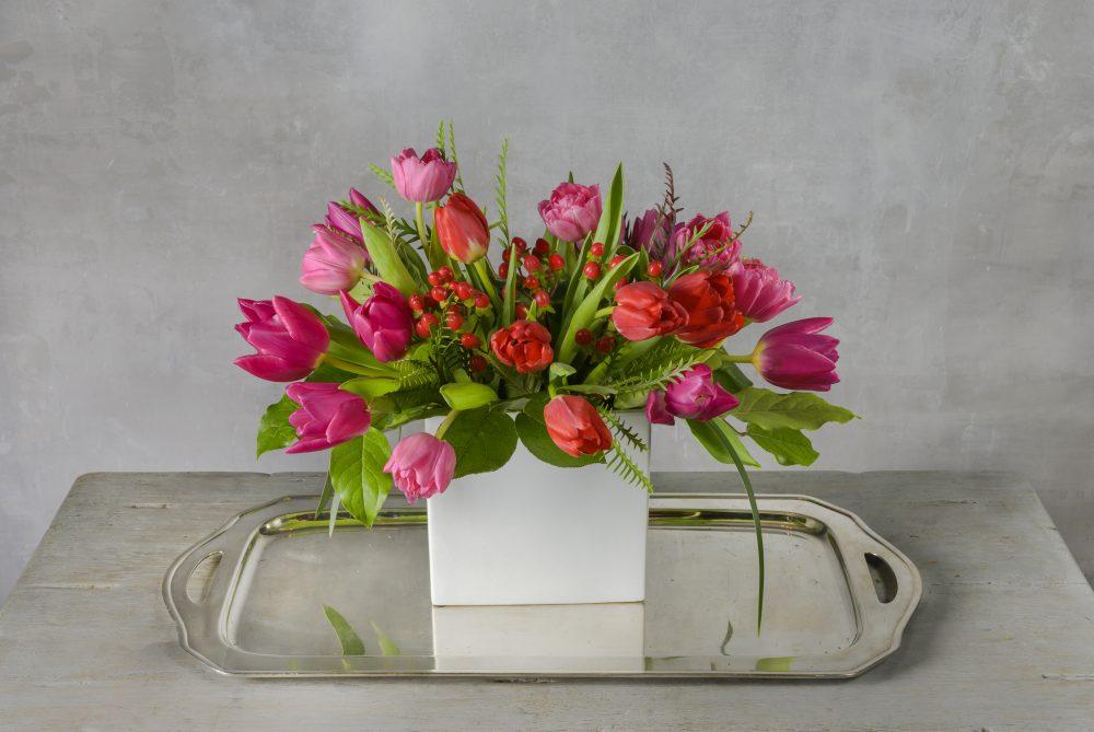 Valentine fresh flower arrangement of bright pink and red tulips in white vase.