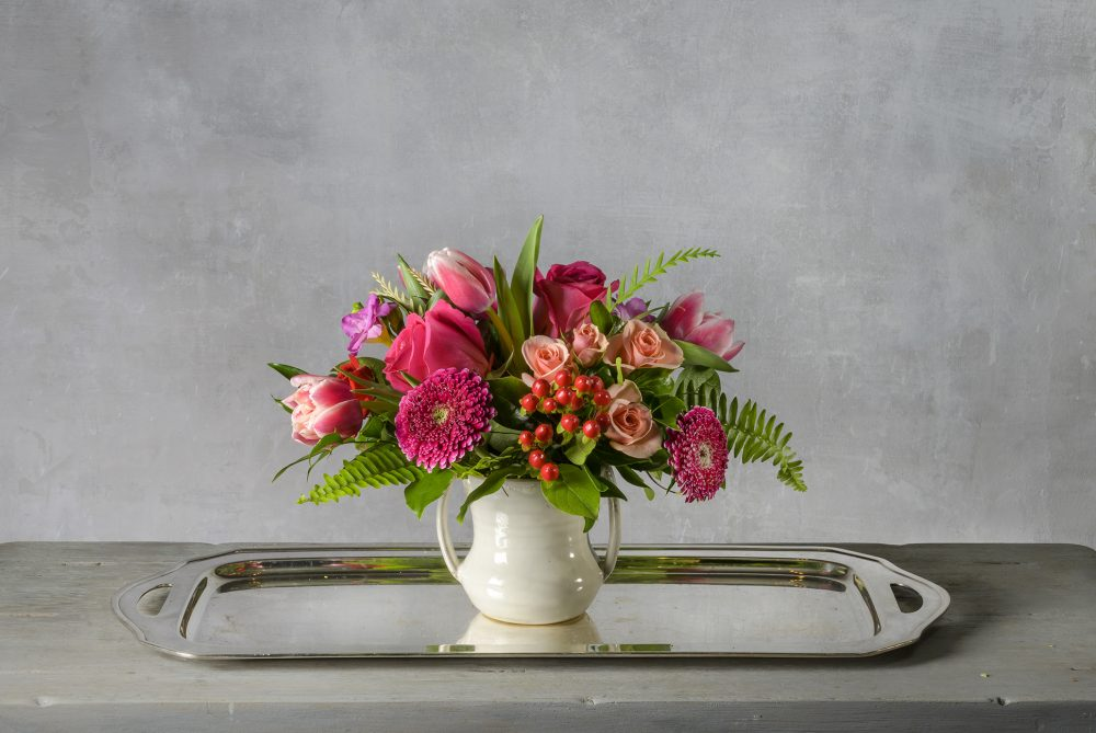 Valentine fresh flower arrangement of bright pink and peach spring blossoms in a ceramic pot.