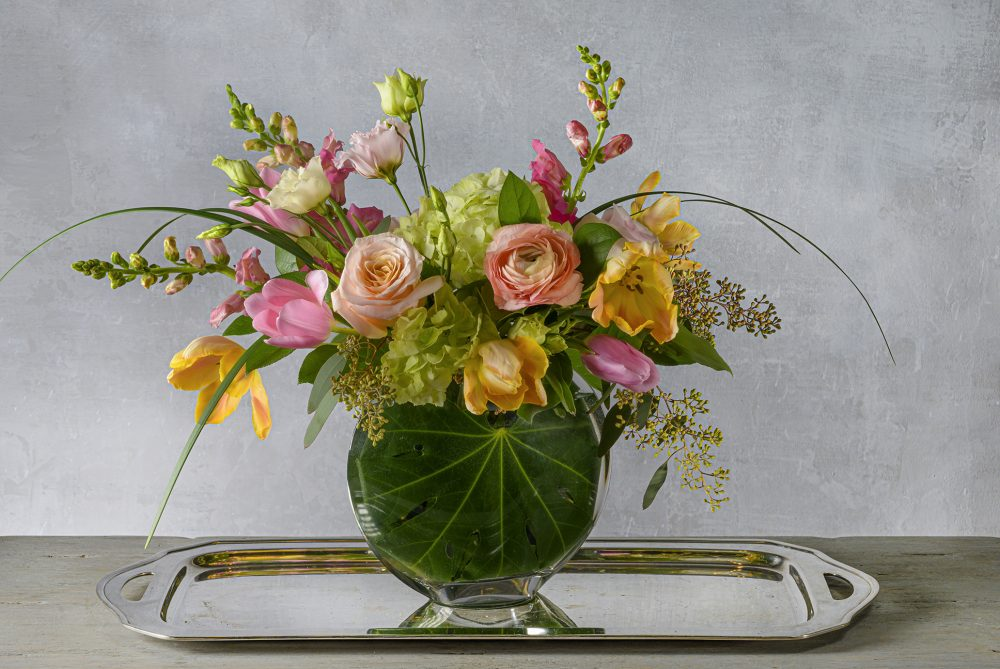 Bright spring blossoms in a taller fresh flower arrangement.