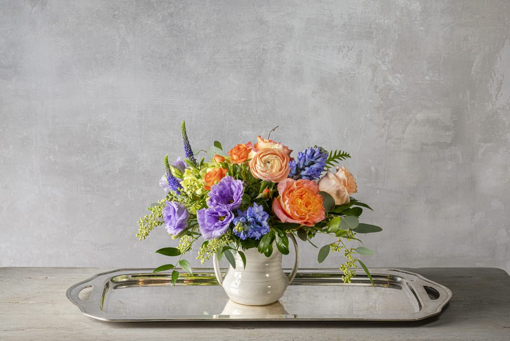 Bright spring blossoms in a petite fresh flower arrangement.