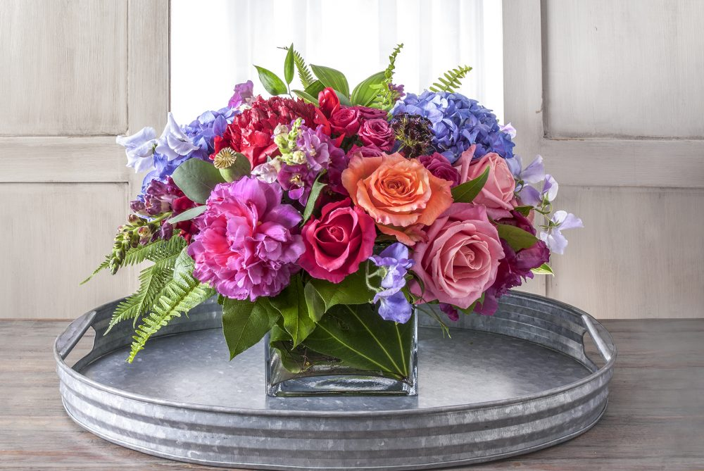Bright spring flowers uniquely arranged with vibrant pink, coral, and purple blossoms.