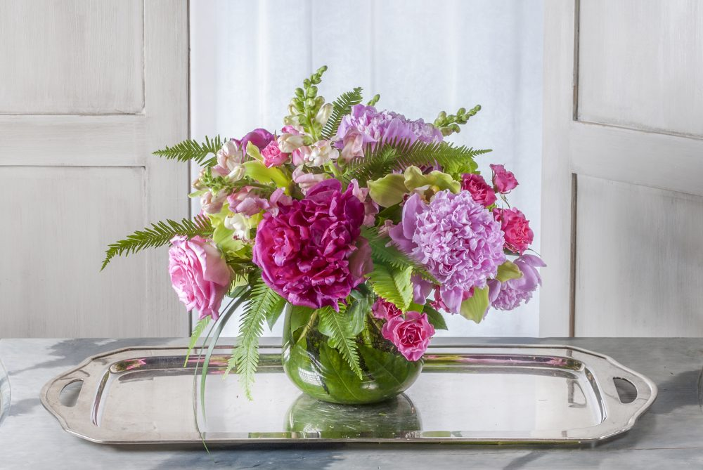 Fresh flowers in bright pink and magenta with seasonal peonies.
