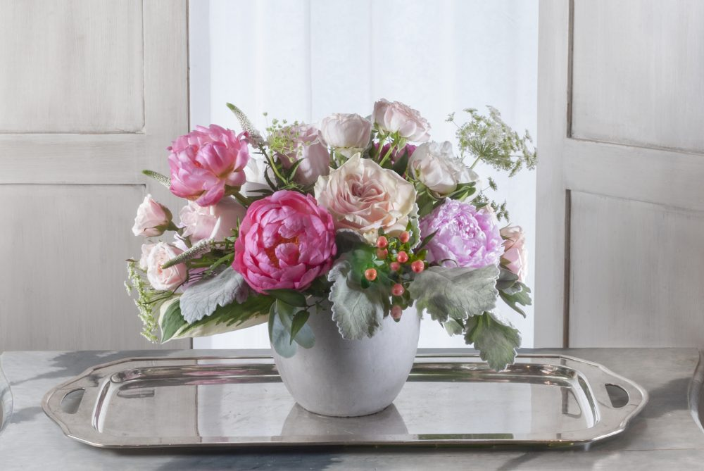 Fresh flowers of blush blossoms and bright pink peonies with silver sage foliage