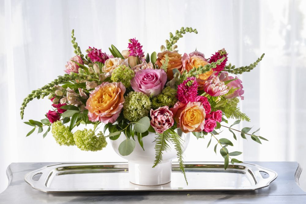 Unique fresh flower arrangement in soft colors of white and peach.