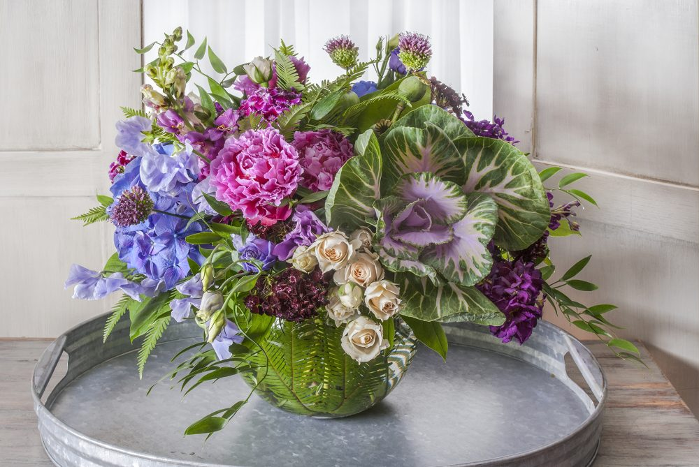 Unique fresh flower seasonal arrangement in bright colors of pink, lavender, and purple.