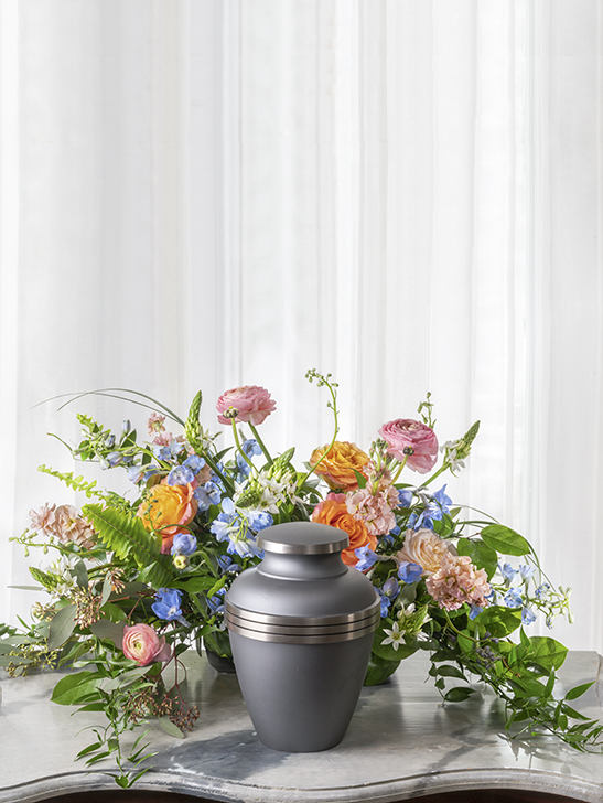 Unique beautiful funeral flower arrangement in a lower garden-style cut flower design to place with a funeral urn.