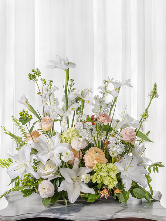 Unique beautiful funeral flower arrangement in a garden-style cut flower design.