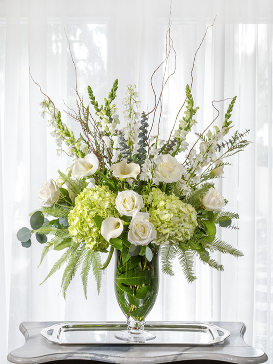 Unique beautiful sympathy flower arrangement of white and green blossoms in a tall design.