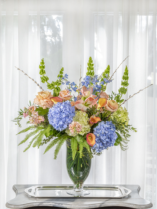 Unique beautiful sympathy flower arrangement of bright pastel colors in a tall design.