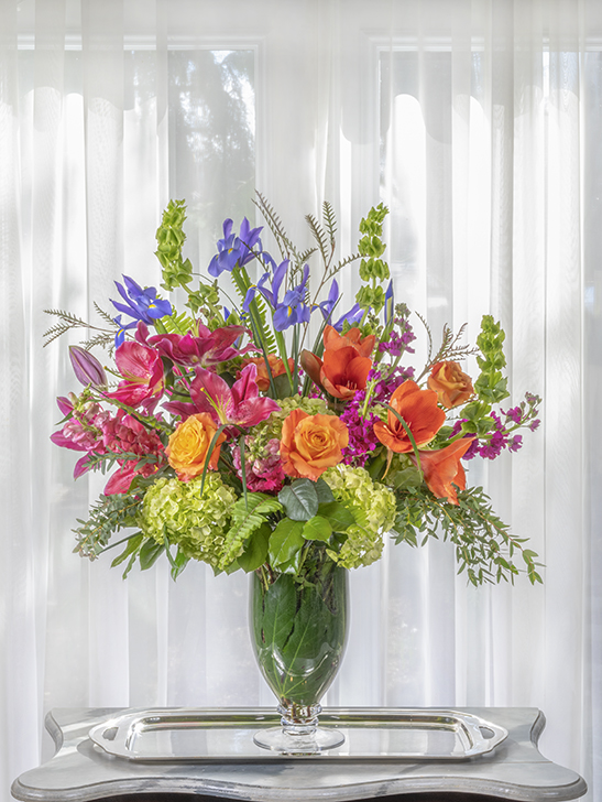 Unique beautiful sympathy flower arrangement of vibrant colors in a tall design.