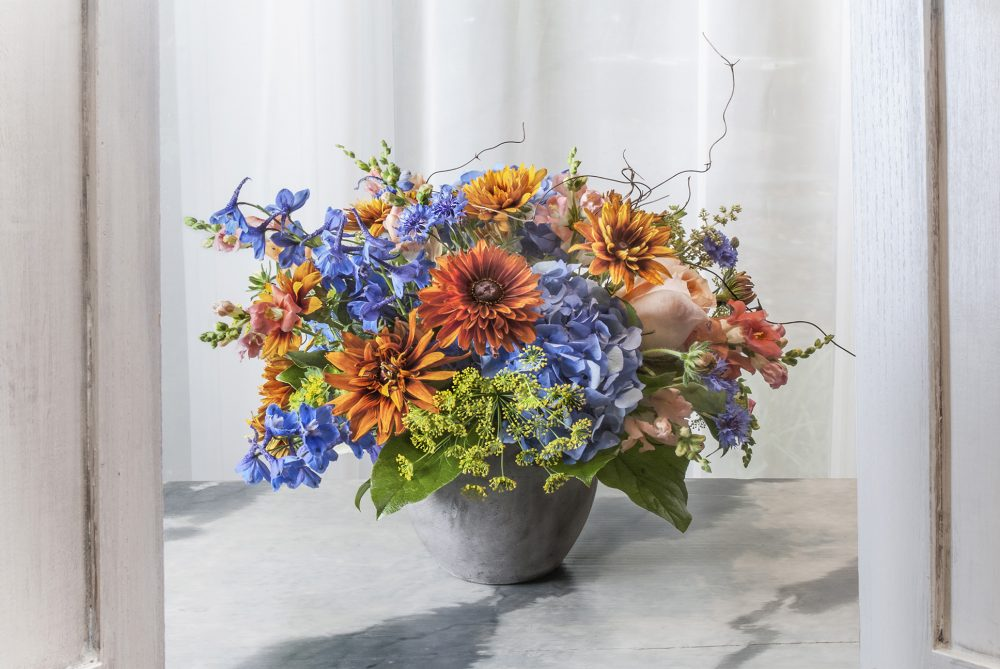 Bright spring flowers uniquely arranged with vibrant blue, gold and yellow, blossoms.