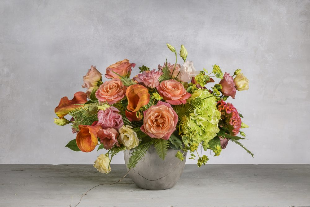 Fresh flowers in bright peach, coral, orange and green seasonal blooms.