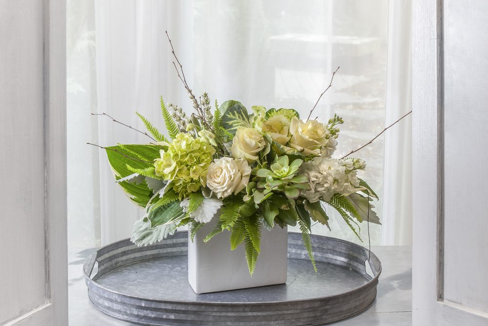 Fresh autumn arrangement in white and green flowers with silver foliage.