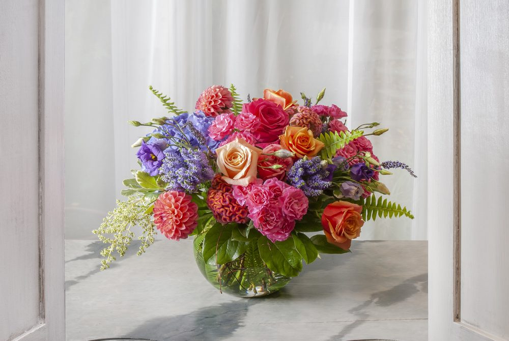 Fresh flowers in bright magenta, coral, and blue with seasonal blooms.