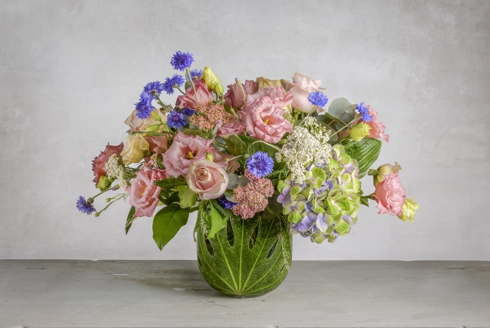 Unique fresh flower arrangement in pretty pink, peach, and blue flowers.