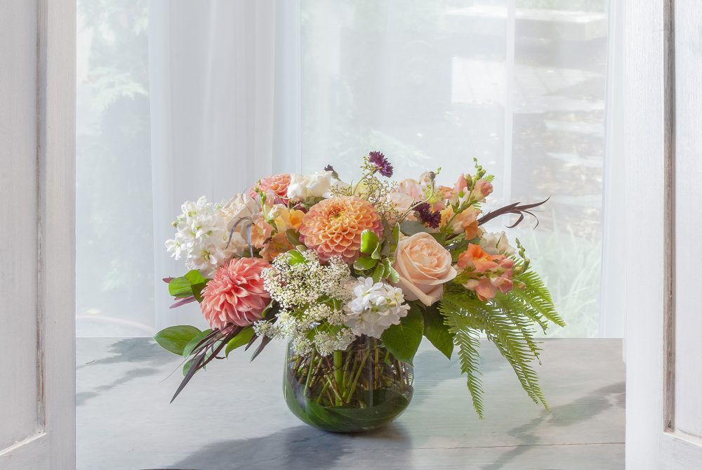 Fresh flowers in bright peach with white seasonal blooms in a leaf wrap.