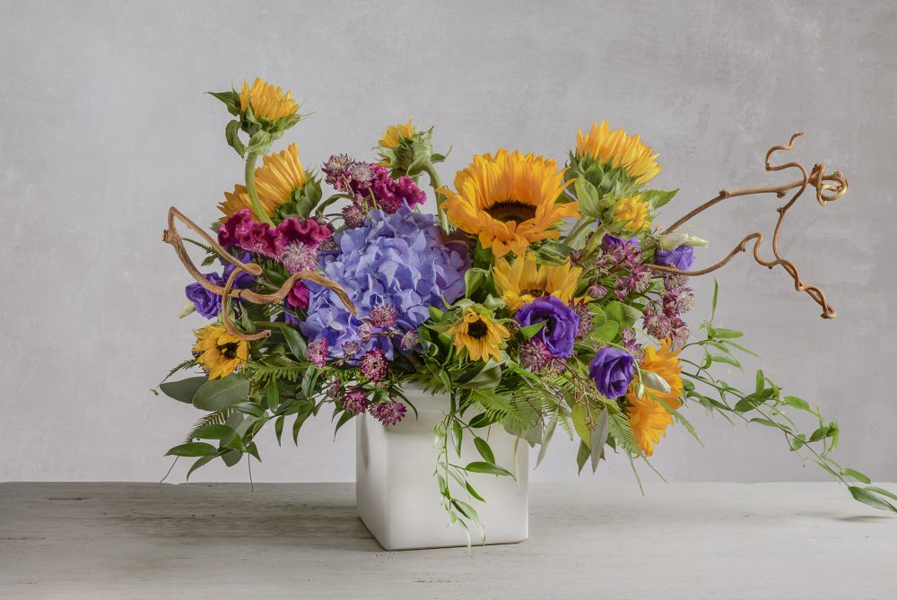 Vibrant summer sunflowers with hydrangea and lush foliage in a garden style arrangement presented in a white square.