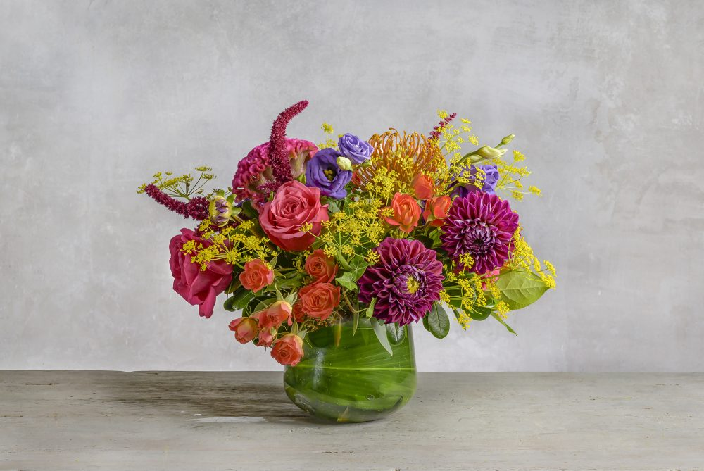 Bold summer flowers with local dahlias and field flowers in a lush arrangement wrapped in emerald leaves.