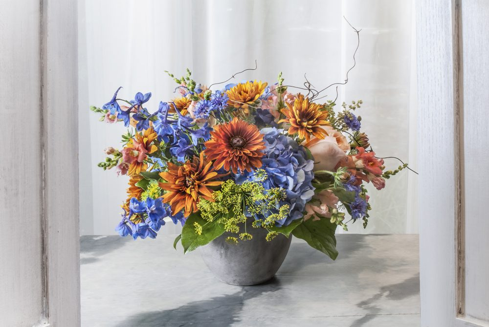 Bright autumn flowers uniquely arranged with vibrant blue, gold and and deep orange blossoms.