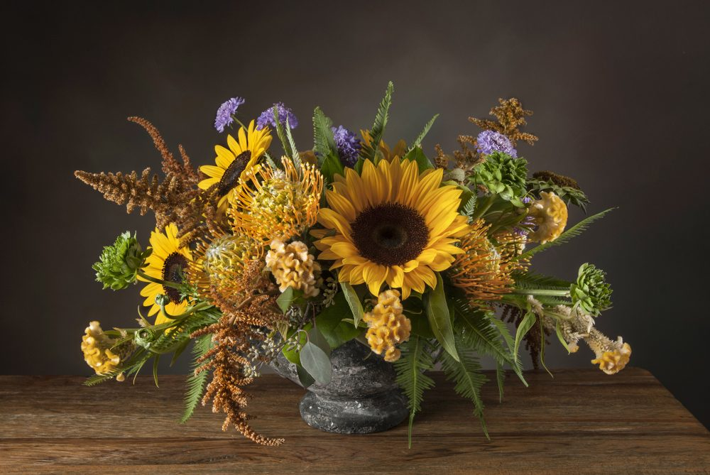 Bright autumn sunflowers in a fresh flower arrangement designed in an aged urn delivered
