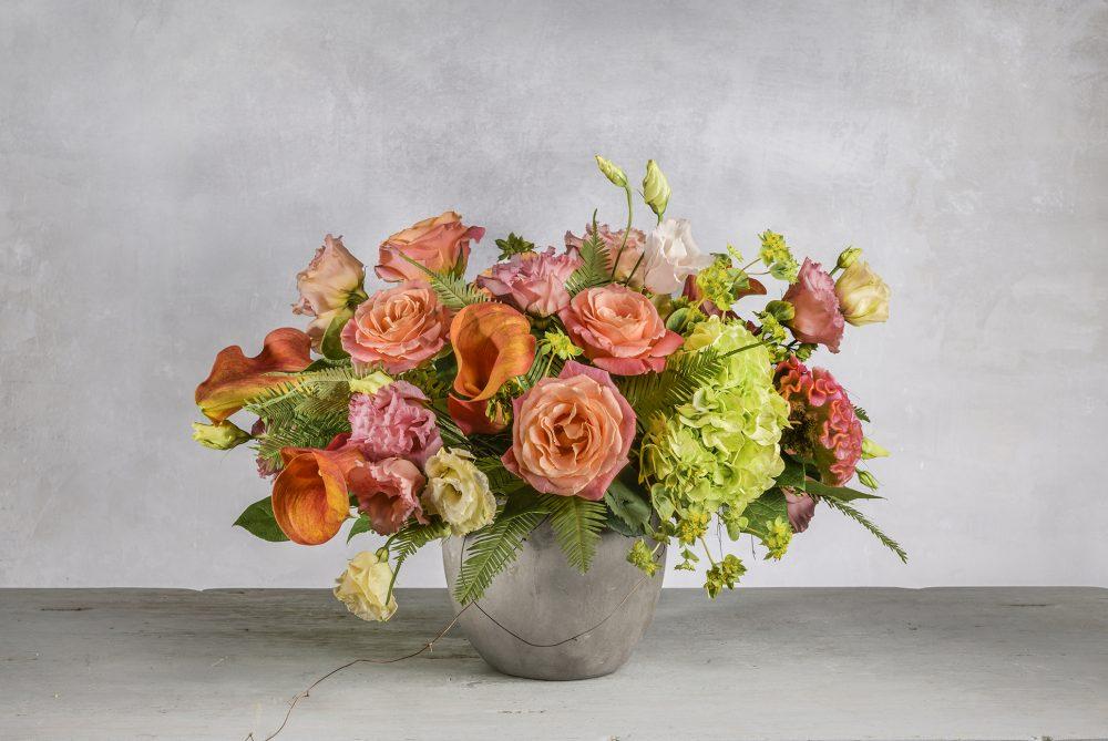 Fresh flowers in bright peach, coral, orange and green seasonal blooms.